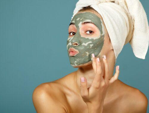 Spa teen girl applying facial clay mask. Beauty treatments.